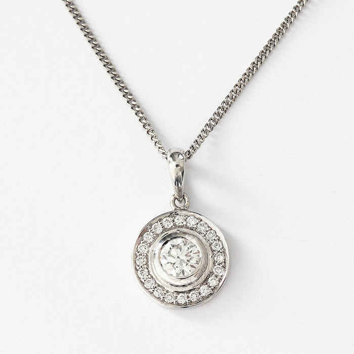 a round diamond cluster pendant on a fine curb link chain 40cm long