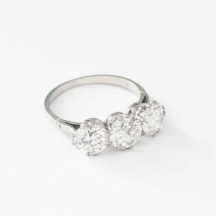 a beautiful diamond set three stone ring in a claw setting with round diamonds and a platinum band