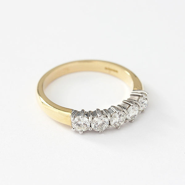 a diamond eternity ring with 5 stones in a claw setting and white gold setting with yellow band