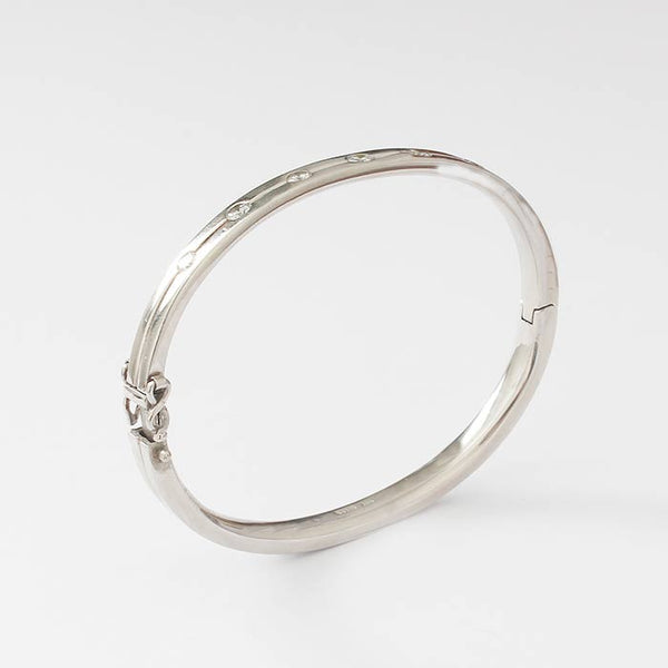 a secondhand diamond set brilliant cut 7 stone oval bangle in platinum