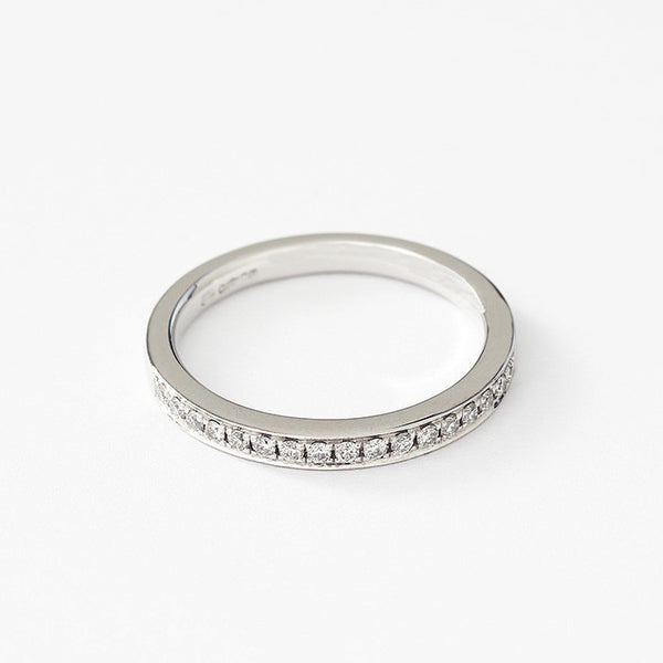 a diamond eternity ring with a claw channel setting in platinum