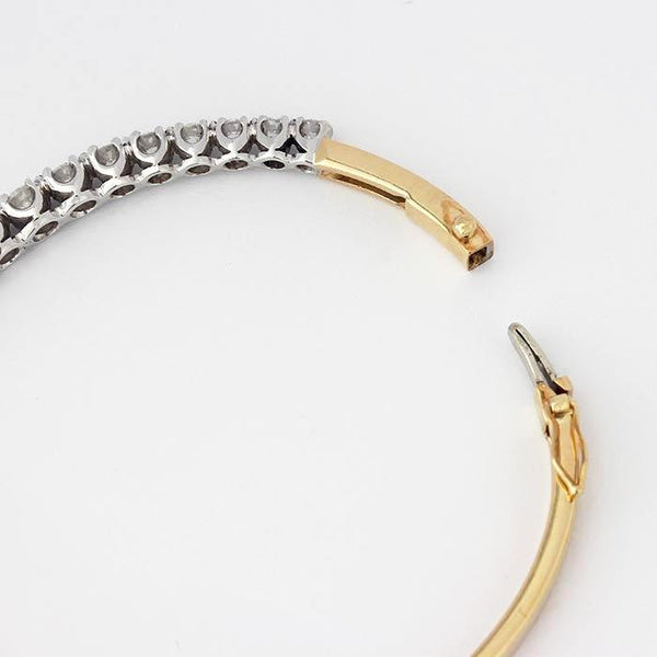 an 18ct yellow and white gold diamond set oval hinged bangle