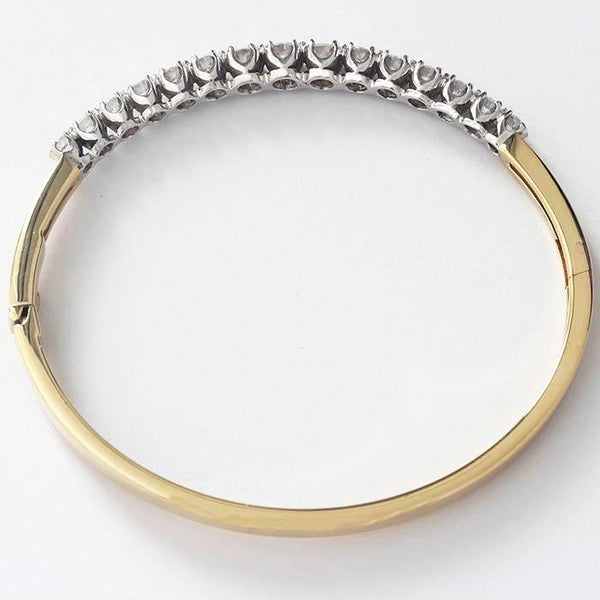 a diamond set hinged bangle made in yellow and white gold settings