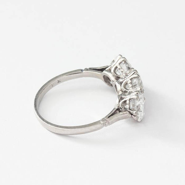 a platinum 3 stone diamond ring with round stones and a claw setting