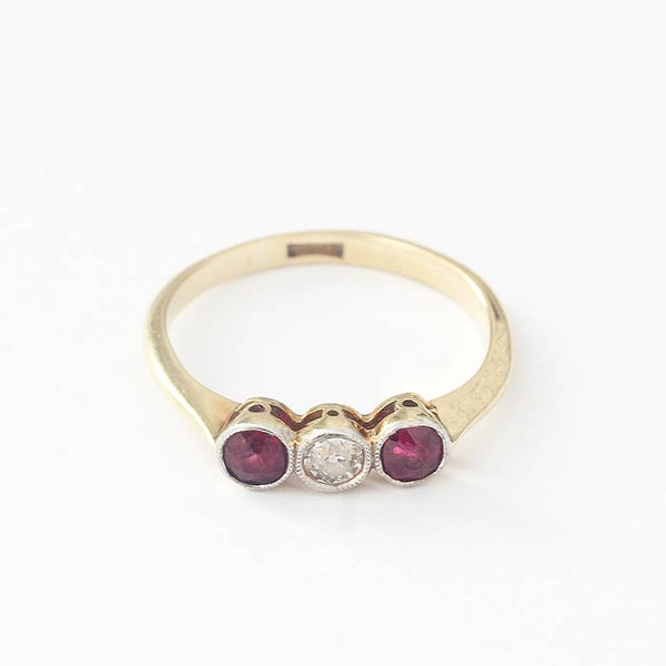 a central round diamond and 2 rubies in a yellow gold band