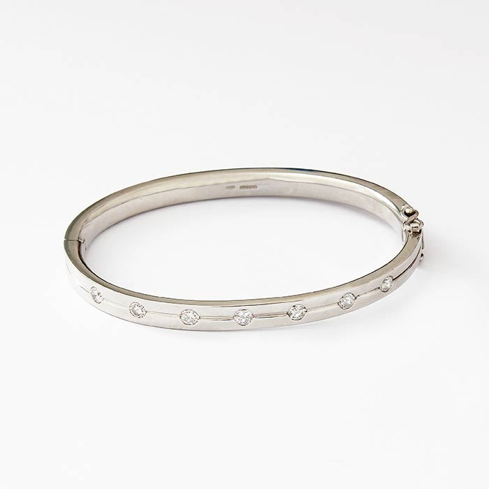 a secondhand platinum set oval hinged bangle with 7 round brilliant cut diamonds on one part
