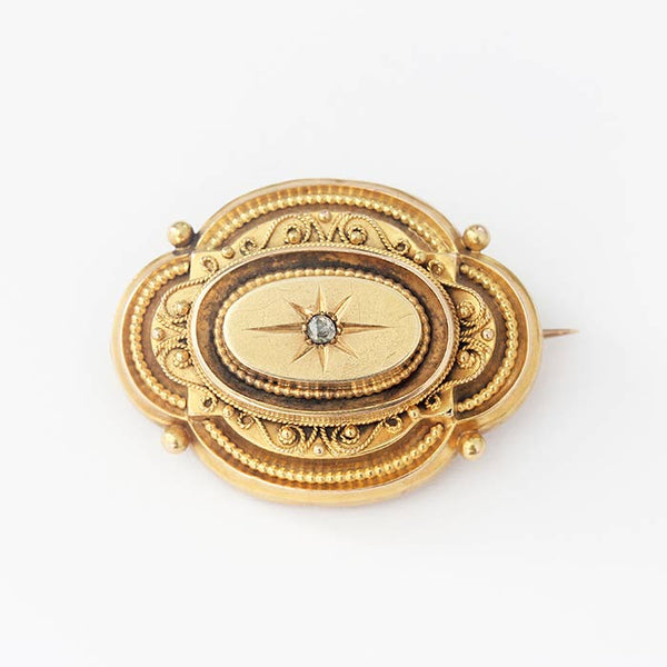 a beautiful yellow gold victorian brooch with a small central diamond and beaded design