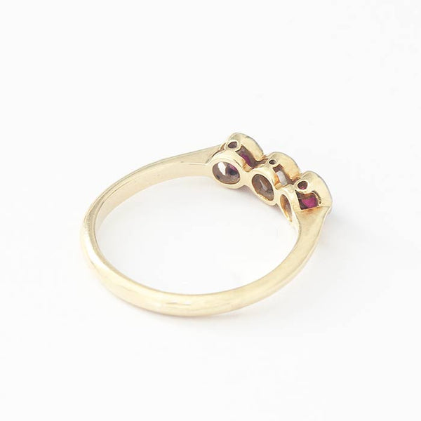 a secondhand vintage yellow gold ring with a central diamond and a round ruby either side