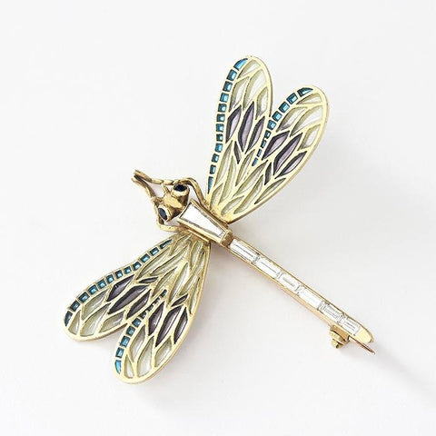 an 18ct yellow gold dragonfly brooch with baguette diamonds and sapphire eyes and enamel  wings which are purple yellow and blue