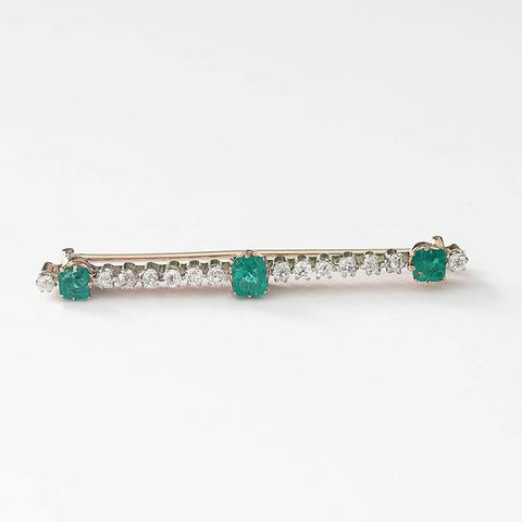 an emerald and diamond bar brooch in yellow and white gold