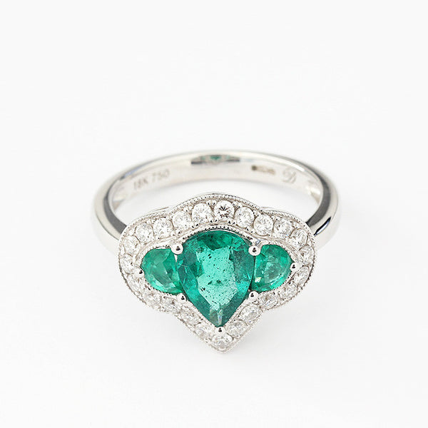 a modern cluster ring with emeralds and diamonds in a claw setting white gold