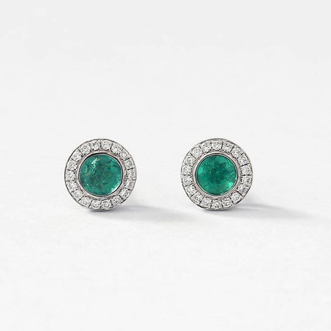 round emerald stud earrings with a surround of diamonds in a white gold setting and post