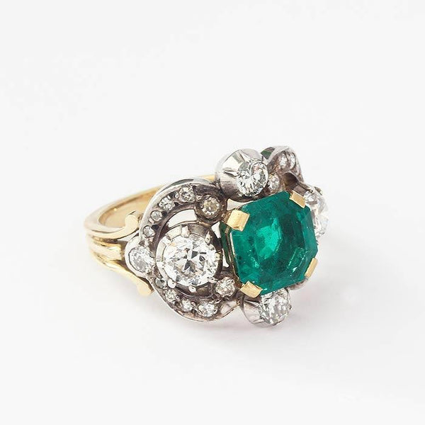 an emerald and diamond beautiful unusual ring with a large square cut emerald and various diamonds in a yellow gold swirl design band