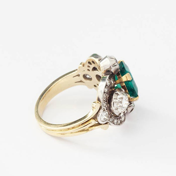 a secondhand emerald and diamond beautiful unusual ring with a large square cut emerald and various diamonds in a yellow gold swirl design band
