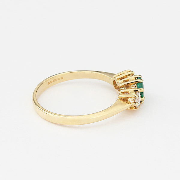 three stone ring with 2 diamonds and 1 emerald in yellow gold