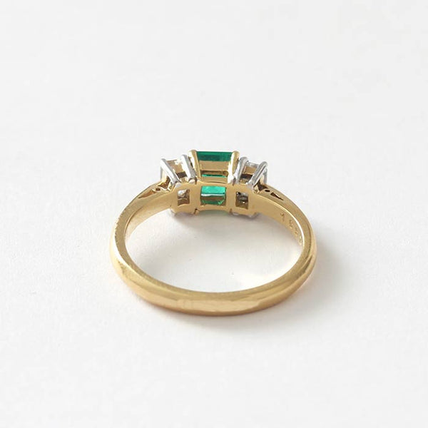 a square emerald with 2 baguette diamonds in a white and yellow setting with a  yellow gold band