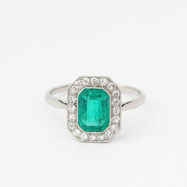 an emerald and diamond cluster ring with grain settings and set in platinum