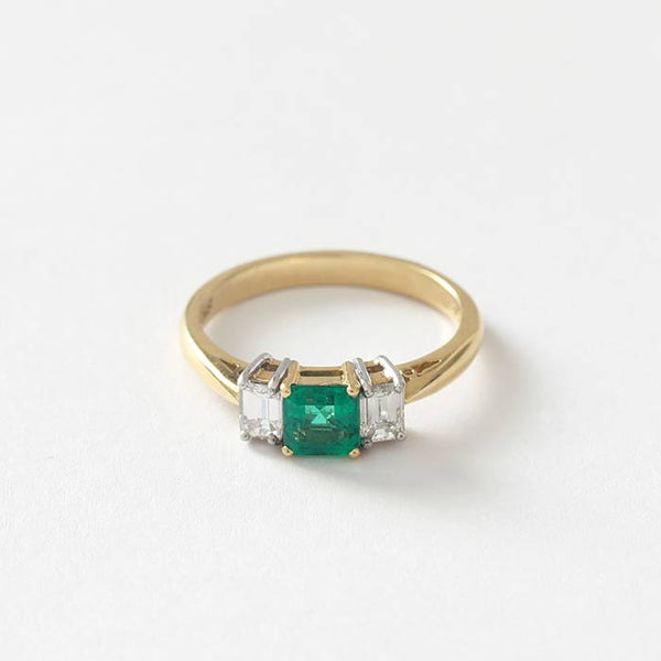 an emerald and diamond 3 stone ring in yellow gold with a central square emerald and baguette diamonds