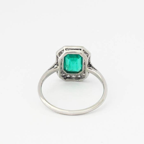 a vintage secondhand emerald and diamond cluster ring in platinum