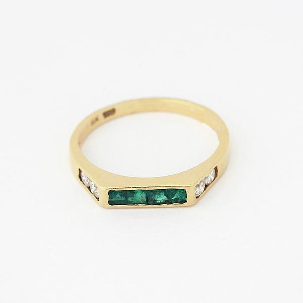 a yellow gold band with 4 square emeralds at the top and 2 round diamonds in each shoulder
