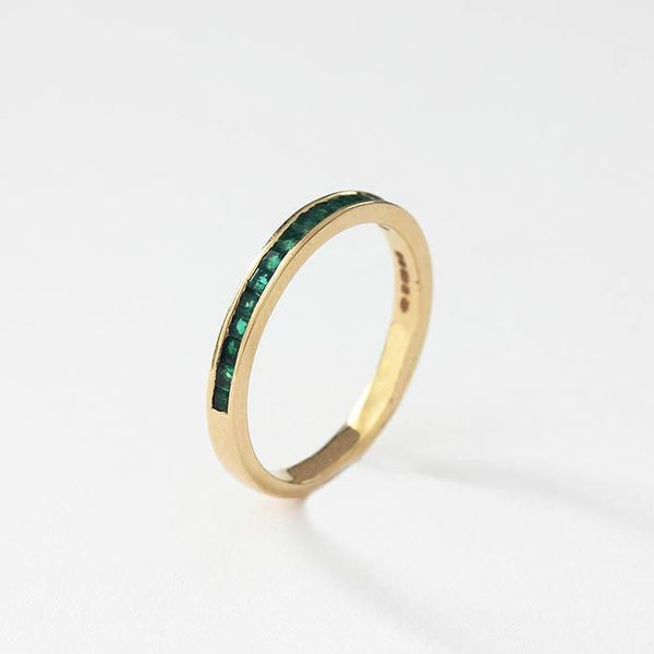 a yellow gold half eternity ring with square cut emerald stones in a channel setting