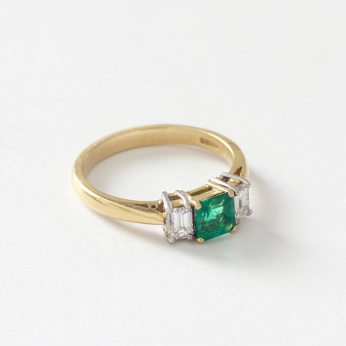 an emerald  and diamond 3 stone ring with a central square emerald and 2 baguette diamonds in a yellow gold band