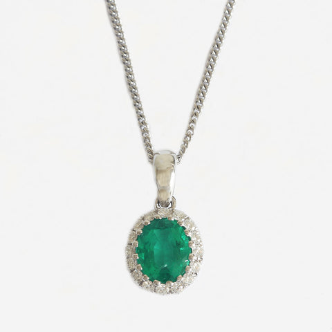 an emerald and diamond claw set oval cluster pendant necklace in white gold