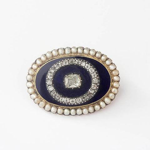 a beautiful oval shaped gold brooch with diamonds pearls and a blue enamel