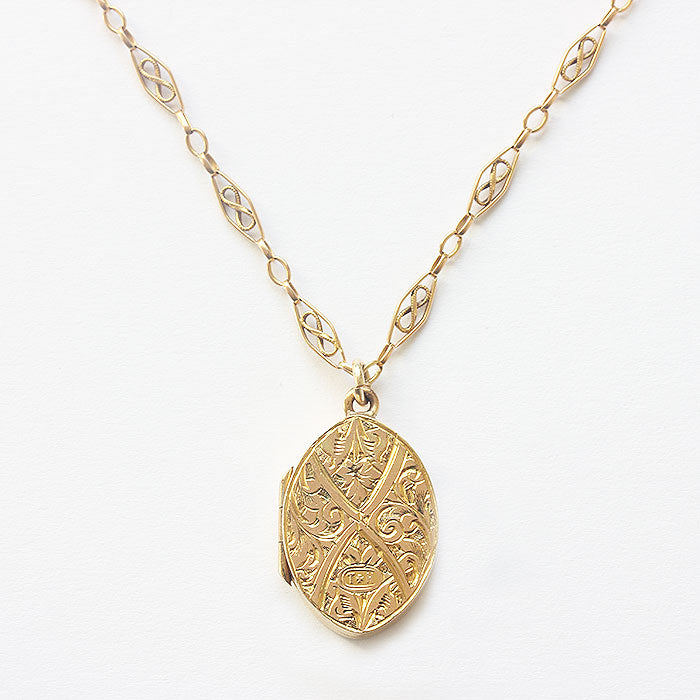 a small oval engraved gold locket with fancy chain in 9 carat gold