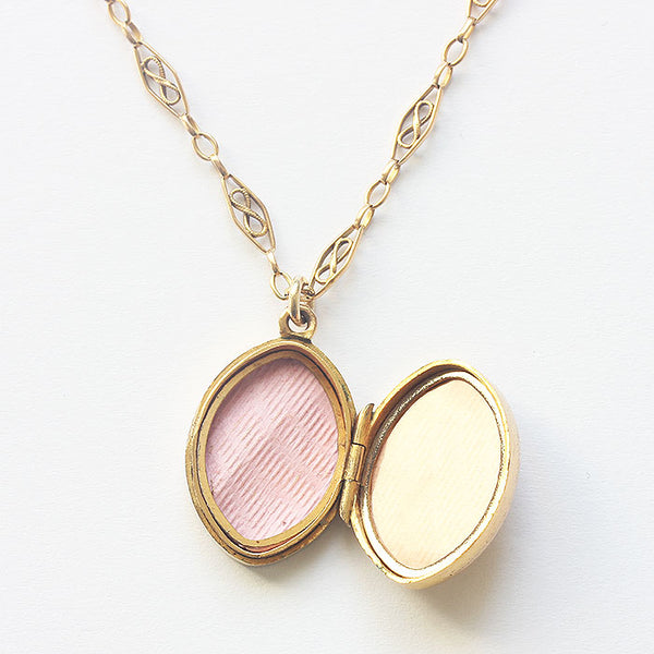 a 9 carat yellow gold engraved oval locket with fancy oval link chain