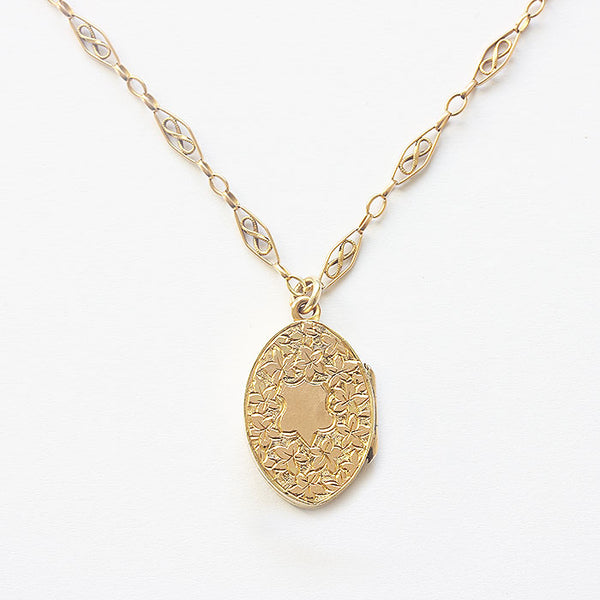 a beautiful engraved leaf design gold locket with oval fancy link chain