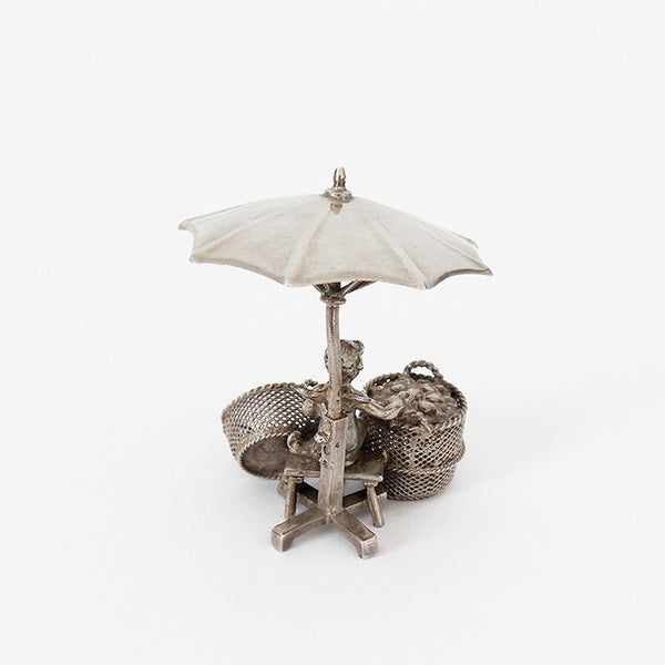 antique ornament with angel sitting under umbrella