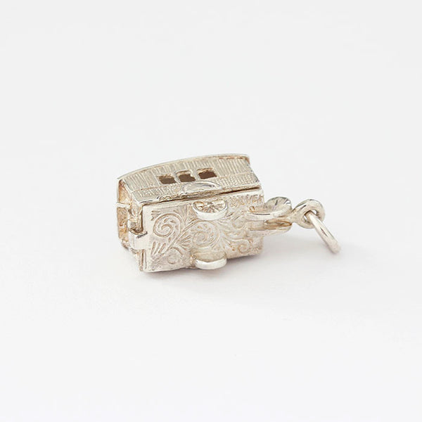a silver caravan charm with pattern and enamel opens up