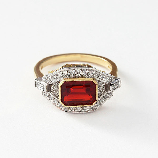 a fire opal and diamond cluster ring in yellow gold with a white setting