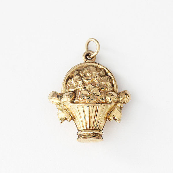a secondhand flowers in a basket charm in yellow gold with 2 ribbons