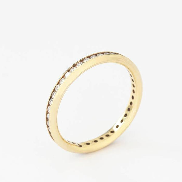 an 18ct yellow gold diamond set full eternity ring with round stones in a channel setting