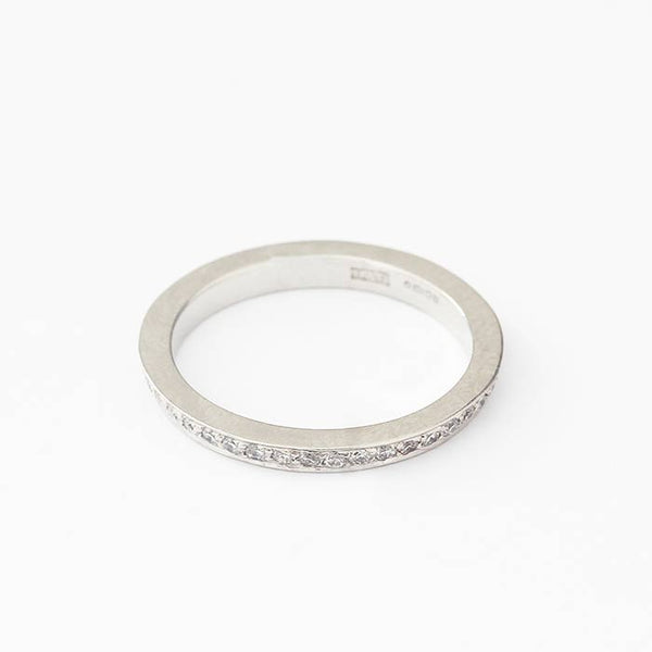 a platinum full eternity ring with small round diamonds in a claw setting