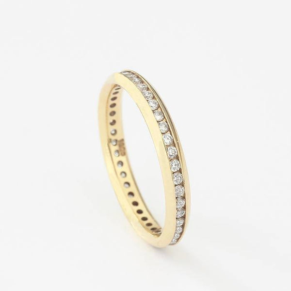 a diamond set full eternity ring in yellow gold with a channel setting