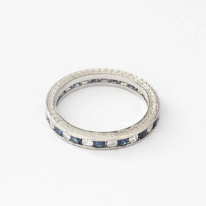 a full eternity ring in white with round sapphires and diamonds in a channel setting with an engraved edge