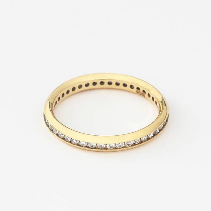 an 18ct yellow gold full eternity ring 2mm wide with small round diamonds in a channel