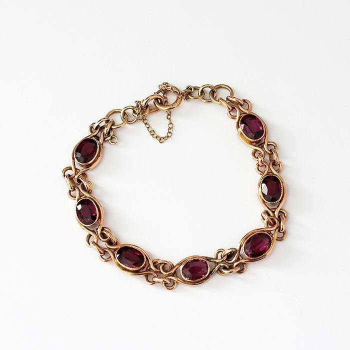 a vintage style garnet set yellow gold bracelet with safety chain attached