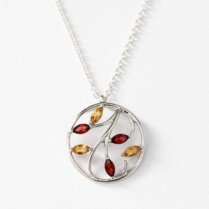 a beautiful citrine and garnet leaf pattern pendant with a silver plain thin round border beneath a fine silver 18 inch trace necklace