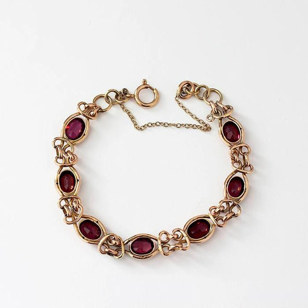 7 oval faceted garnets in a rub over setting with a gold bracelet and safety chain