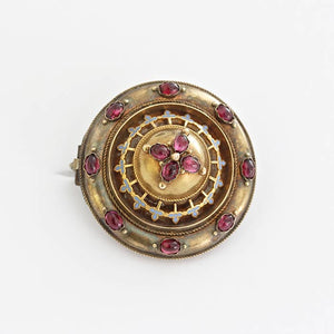 an Etruscan design target brooch with cabochon garnet stones and blue enamel detailing