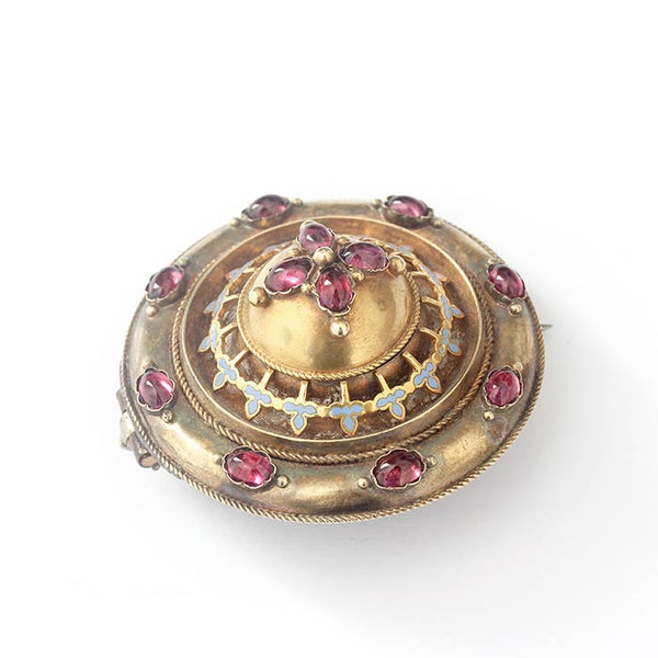 a 9 carat secondhand garnet target Etruscan brooch with blue enamel detailing and roped edge