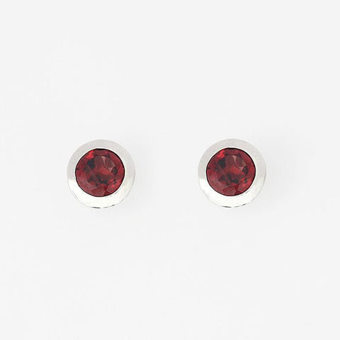 round garnet stud earrings in silver with a rub over setting