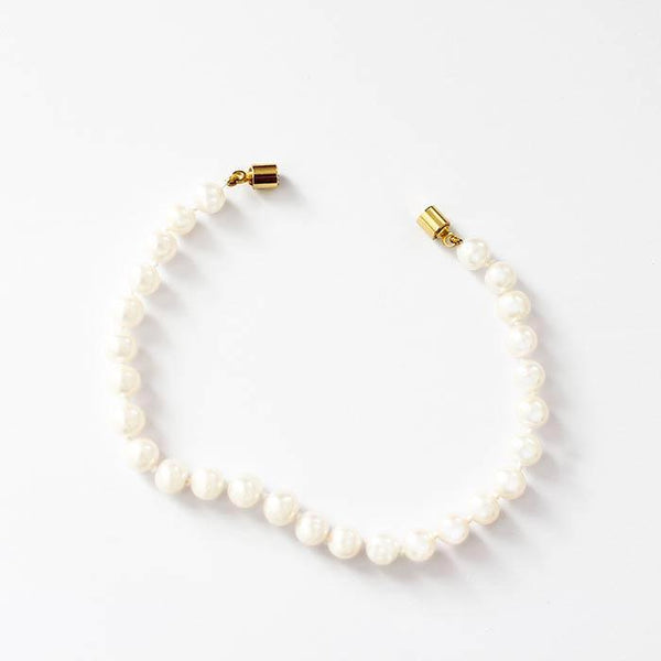 a secondhand pearl bracelet with 27 uniform freshwater pearls with a yellow gilt metal magnetic clasp