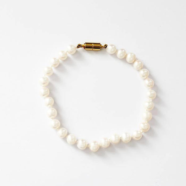 a secondhand  row of freshwater pearls on a gilt metal magnetic clasp on a bracelet threaded knotted