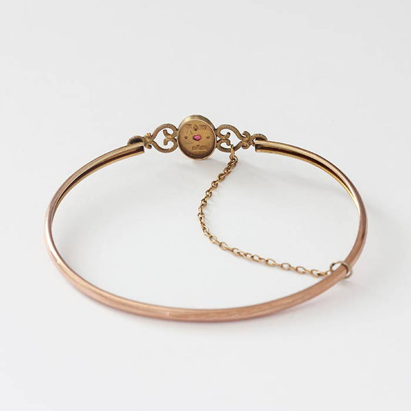 a preloved ruby and pearl antique yellow gold and rose gold bangle with safety catch