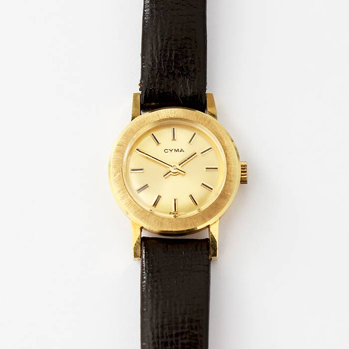 a ladies CYMA gold cased watch with a black leather strap and original tag
